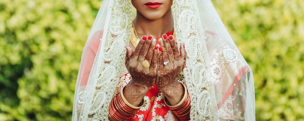 La mariée hindoue au voile blanc lève les mains au ciel Photo gratuit