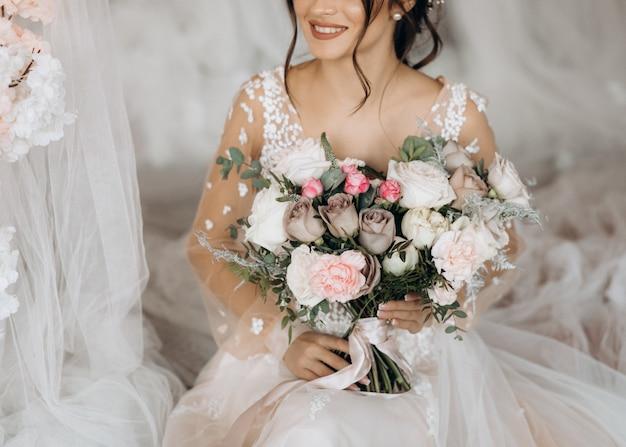 Mariée de luxe tenant un grand bouquet de fleurs Photo gratuit