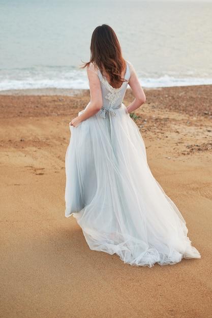Mariée Marchant Le Long De La Côte Vêtue D'une Belle Robe De Mariée Photo Premium