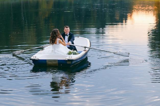 La Mariée Et Le Marié Dans Une Barque Sur Le Lac Photo Premium