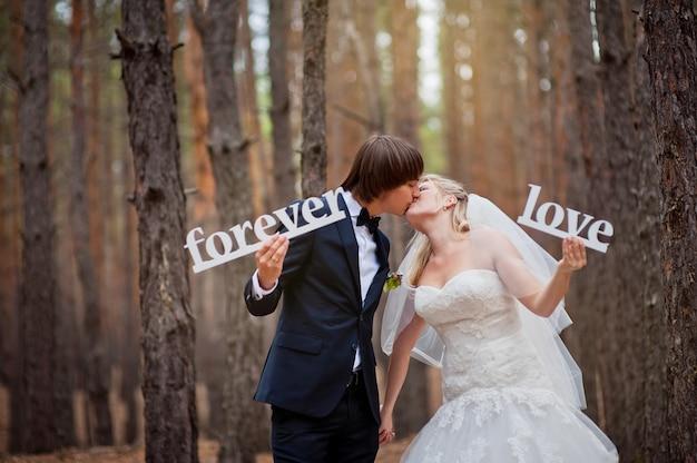 Mariée et le marié dans une forêt de pins en automne Photo Premium