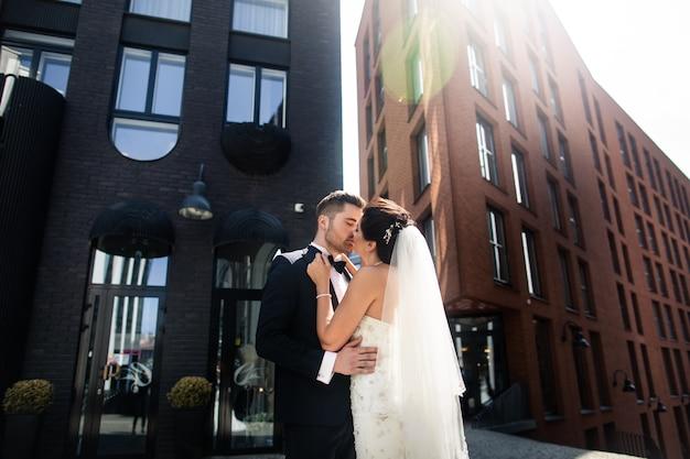 Mariée et le marié marchant dans la ville, le jour du mariage, le mariage. mariée et le marié en milieu urbain. jeune couple au jour du mariage. Photo Premium