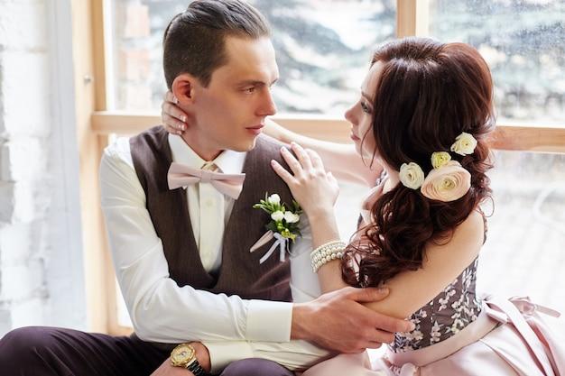 Mariée et le marié près de grande fenêtre étreignant l'amour Photo Premium