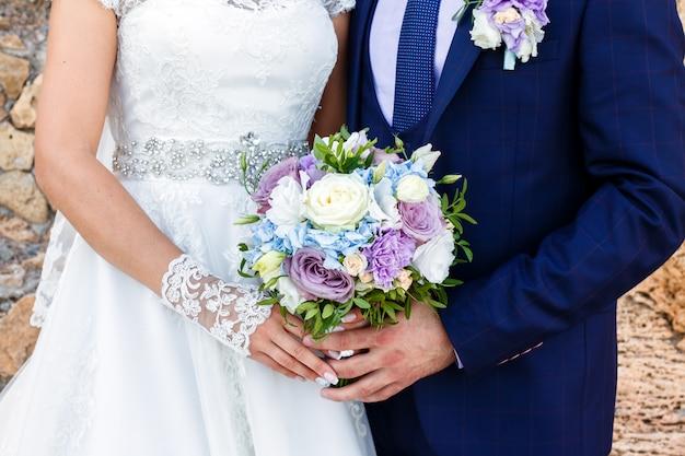 Mariée et le marié tenant beau bouquet de roses en plein air. Photo Premium