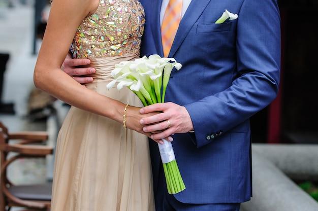 Mariée Et Marié Tenant Un Bouquet De Mariage De Callas. Photo Premium