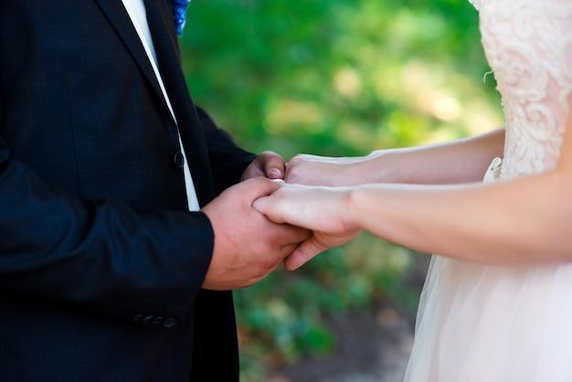 Mariée et le marié tenant par la main au jour du mariage. Photo Premium