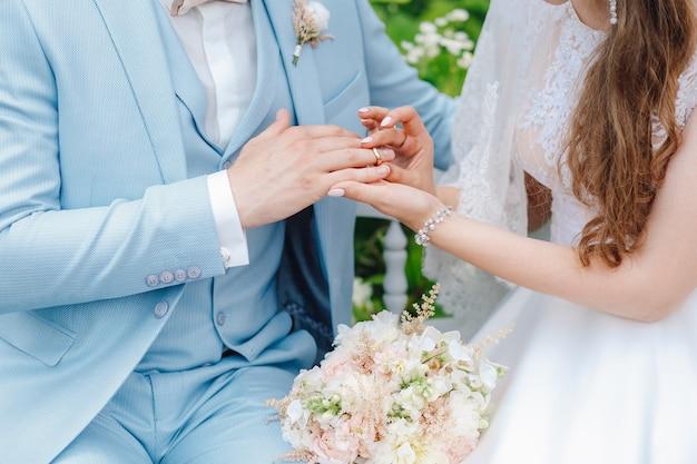 La mariée met la bague de son époux en gros plan Photo Premium