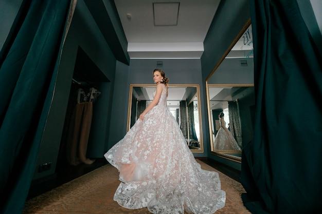 Mariée De Mode En Robe De Mariée Blanche Posant Dans La Cabine D'essayage. Photo Premium