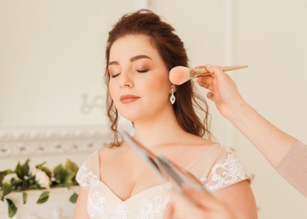 La mariée prépare son maquillage Photo gratuit