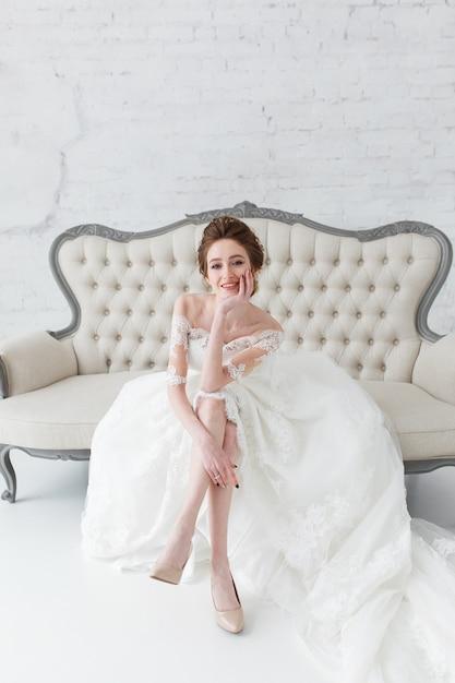 Mariée regardant par la fenêtre, elle attend le marié assis sur un grand canapé classique. Photo gratuit