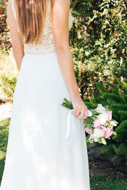 Mariée en robe blanche tenant un bouquet de fleurs à la main Photo gratuit