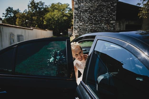 La mariée s'assoit dans la voiture Photo gratuit