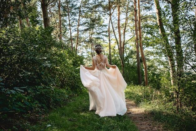 La mariée s'enfuit par la route forestière habille le vent Photo Premium