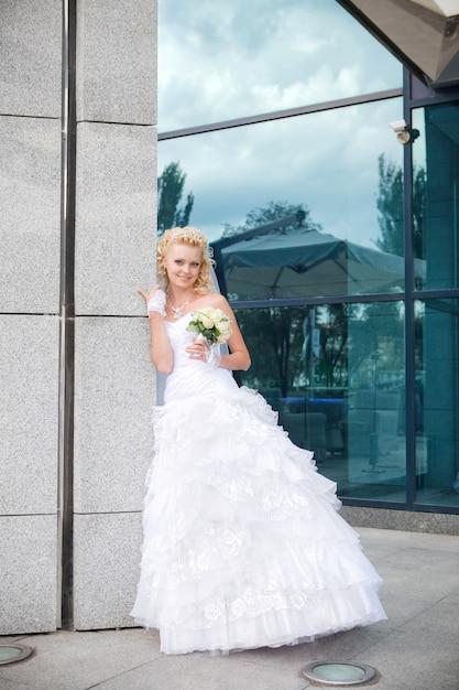 La mariée se tenir à une colonne du bâtiment et de la réflexion dans le verre Photo Premium