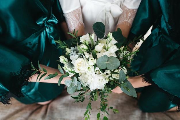 La mariée et ses amies tiennent un bouquet de mariée Photo gratuit