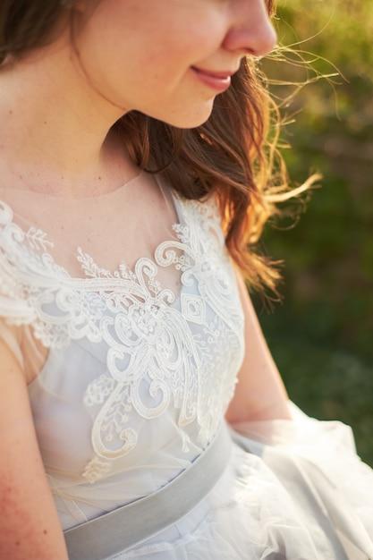 Mariée souriante tenant le bord d'une robe Photo Premium