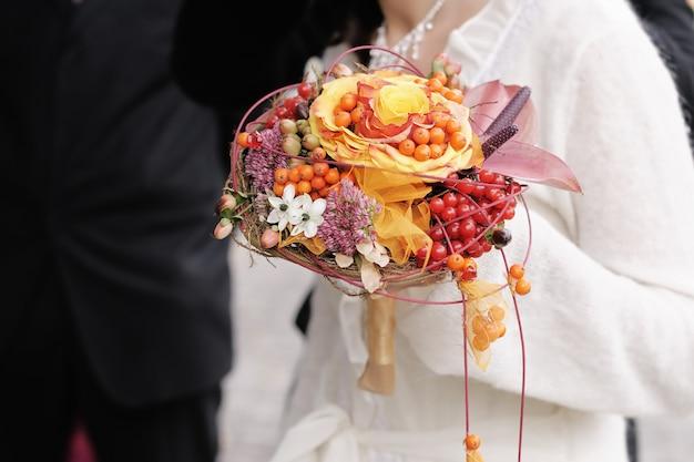 Mariée tenant beau bouquet de fleurs de mariage orange Photo Premium