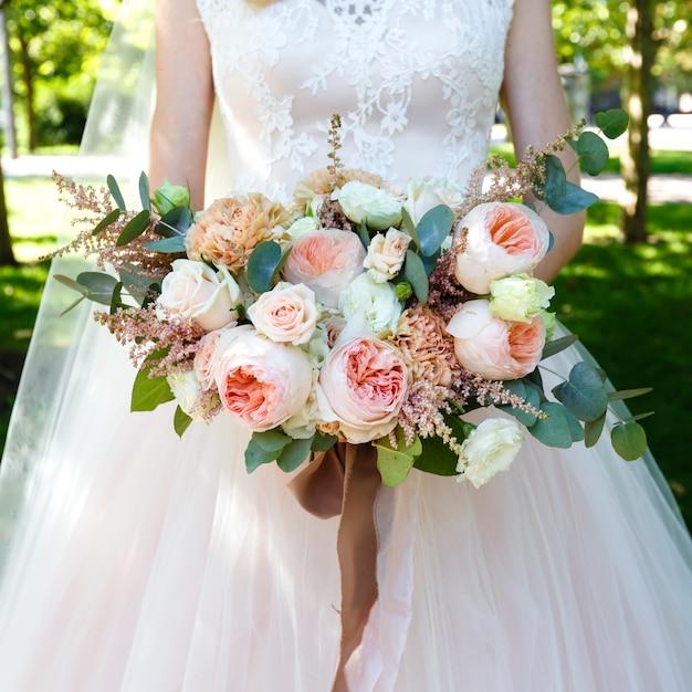 Mariée tenant beau grand bouquet de roses en plein air. cadre carré. Photo Premium