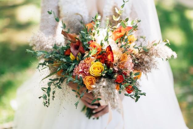 Mariée Tenant Un Gros Bouquet De Mariée. Bouquet De Fleurs Automnales Photo Premium