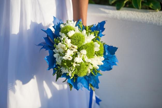 La mariée tient un bouquet de mariage dans les couleurs blanches et vertes et un décor bleu. Photo Premium