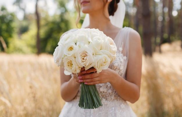 La mariée tient un bouquet de mariage de fleurs blanches en plein air jeune fille dans une robe blanche Photo Premium