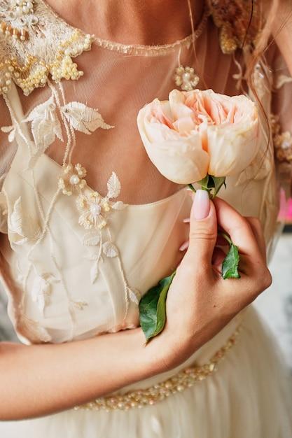 La mariée tient une fleur rose dans les mains Photo Premium