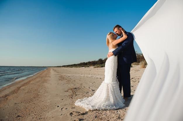 Les Mariés Au Bord De La Mer Le Jour De Leur Mariage. Photo Premium