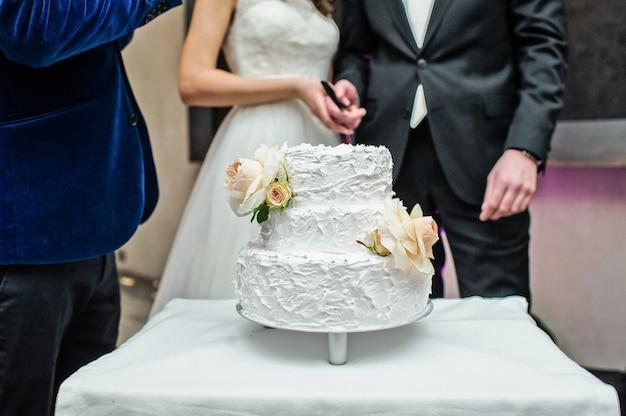 Les mariés coupent le gâteau de mariage traditionnel Photo Premium