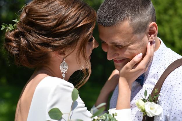 Les mariés dans un bouquet baiser dans un parc verdoyant Photo Premium