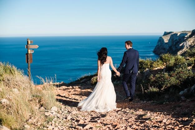 Les mariés marchant sur la plage et se tenant la main. Photo Premium