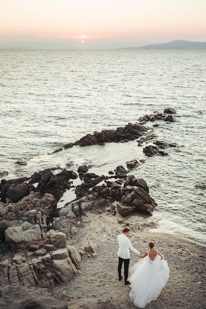 Les mariés marchent vers le coucher de soleil sur la mer Photo gratuit