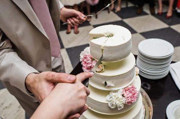 Les mariés ont coupé le gâteau de mariage lors d'un banquet dans un restaurant Photo Premium