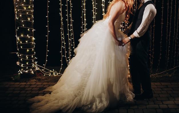 Les mariés s'embrassent debout devant le mur de lumières Photo gratuit