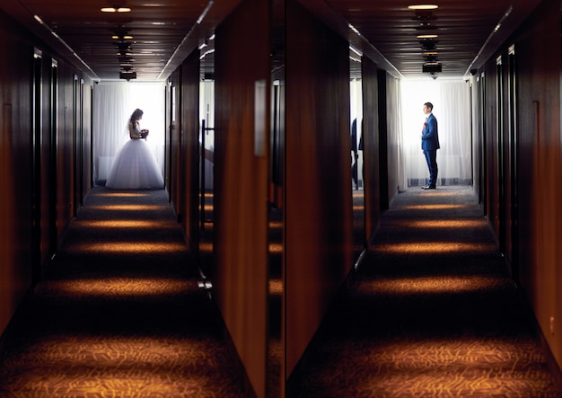 Les mariés se tiennent dans le couloir sombre Photo Premium