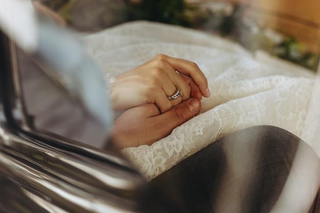 Les mariés se tiennent par la main, assis à l'intérieur de la voiture Photo gratuit