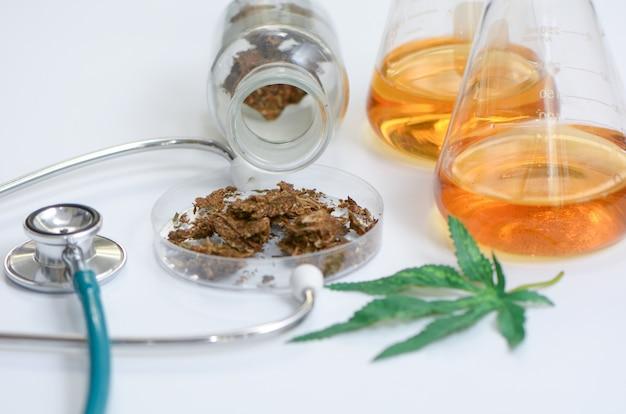 Marijuana, cannabis avec comprimés comprimés et stéthoscope. Photo Premium