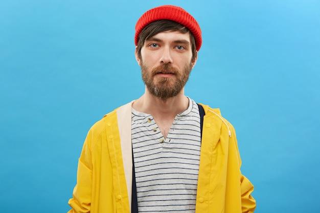 Marin Barbu Habillé En Chapeau Rouge Et Anorak Jaune Posant Contre Le Mur Bleu. Homme Sérieux Avec Barbe Aux Yeux Bleus Charmants Photo gratuit