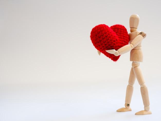 Marionnette En Bois Debout Et Tenant Un Coeur Rouge Sur Le