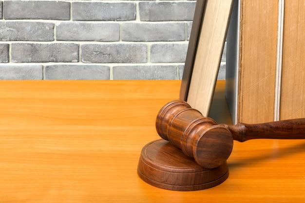 Marteau en bois et livres sur une table en bois Photo Premium