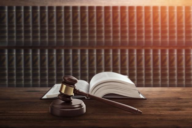 Le marteau du juge et un livre sur une table en bois. Photo Premium