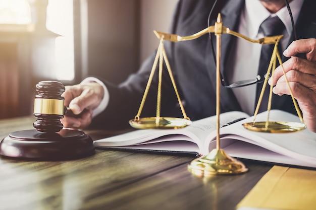 Marteau sur une table en bois et avocat ou avocat travaillant sur des documents. droit juridique Photo Premium