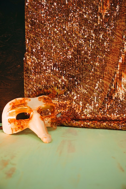 Masque De Carnaval Blanc Près Du Textile Paillettes Dorées Scintillantes Sur Une Surface Patinée Verte Photo gratuit