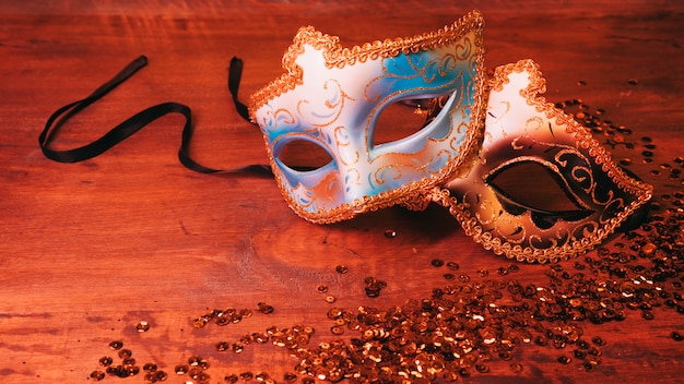 Masque de carnaval deux bleu et or avec des paillettes scintillantes sur le bureau en bois Photo gratuit