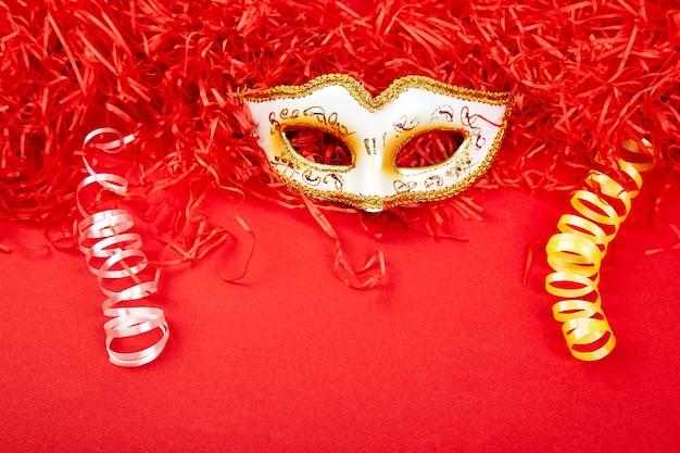 Masque de carnaval jaune et blanc sur fond rouge. Photo Premium
