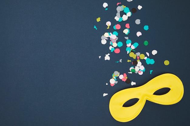 Masque de carnaval jaune et confettis multicolores sur fond coloré Photo gratuit