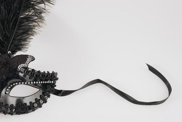 Masque de carnaval noir avec plume sur table lumineuse Photo gratuit