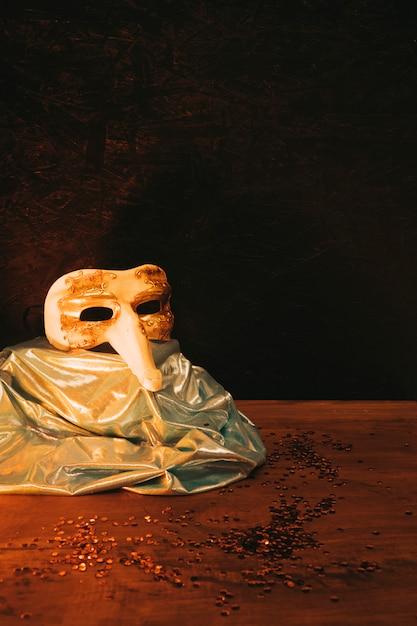 Masque de carnaval or vintage avec paillettes sombres sur fond Photo gratuit