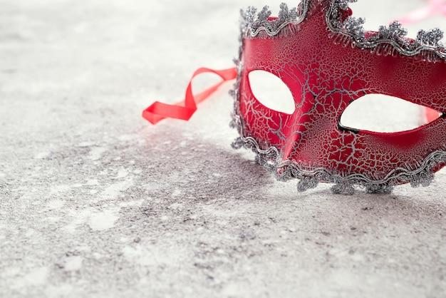 Masque de carnaval rouge magnifique pour concept de fond de vacances de carnaval sur pierre Photo Premium