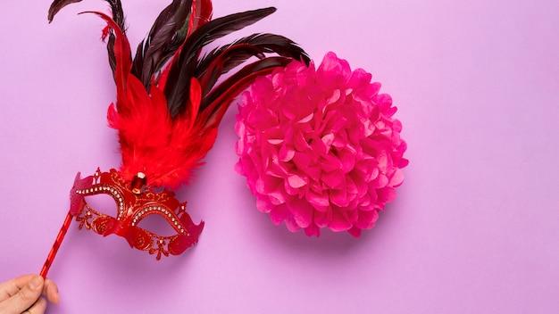 Masque De Carnaval Rouge Avec Des Plumes Sur Fond Rose Photo gratuit