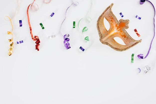 Masque de carnaval avec des rubans colorés sur la table Photo gratuit